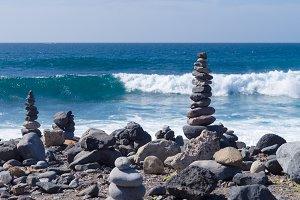Cairn against ocean wave