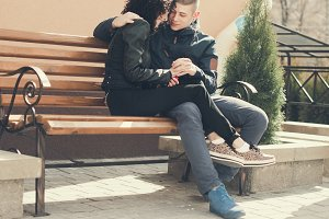 beautiful couple sits on a bench