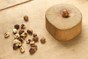 Hazelnuts and anvil on wooden background