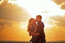 Loving couple kissing at sunset.