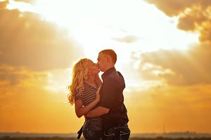 Loving couple kissing at sunset.
