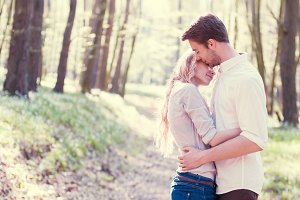 Happy couple hugging in a forest