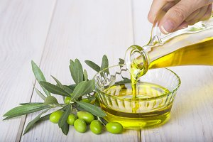 Bottle pouring virgin extra olive oil in a bowl