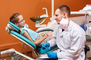 Dentist and child in dental clinic