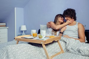 Couple smiling and hugging after eat breakfast in bed