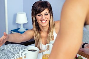 Surprised woman in bed looking to breakfast served by man