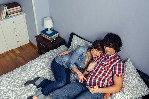 Couple in love looking electronic tablet on bed