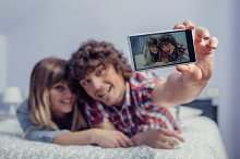 Couple in love taking selfie with smartphone on bed