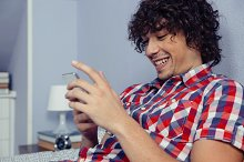 Young handsome man looking smartphone and laughing
