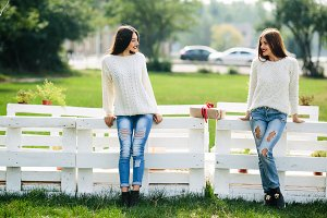 Two girls lean bench