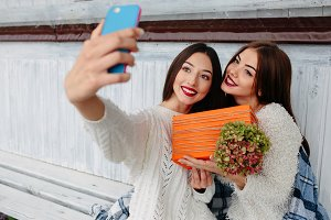 Two girls make selfie with gift
