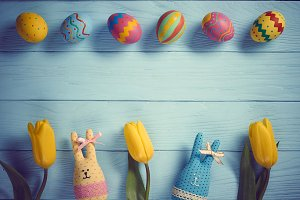 Easter background, eggs, rabbits, tulips on wood