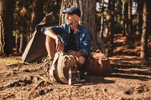 Mature man sitting alone at campsite