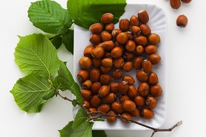 hazelnuts in plate on white