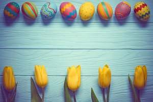 Easter background, eggs, yellow tulips on wood
