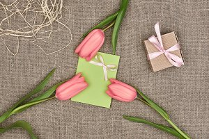 Mothers Day background. Tulips, note on sackcloth