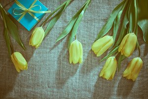 Mothers Day background. Tulips, gift on sackcloth