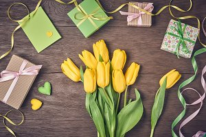 Mothers Day background. Tulips, gift boxes on wood
