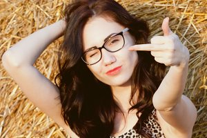 girl with glasses shows rude gesture