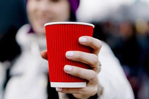 Girl holds a red cup of hot tea