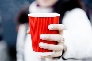 Girl holds a red cup of hot coffee