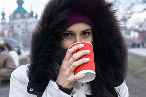 Girl drinks a red cup of hot coffee