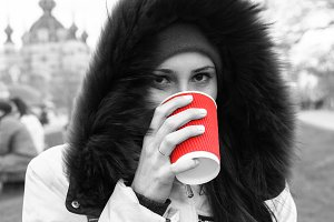 Girl drinks a red cup of hot tea