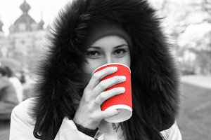 Young girl and red cup of hot coffee