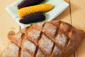 Close up of fresh whole wheat bread laying in green white napkin on wooden table with black and yellow corn