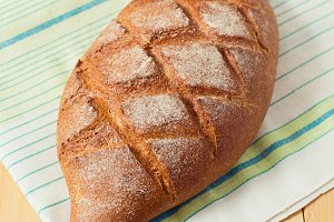 Close up of fresh whole wheat bread laying in green white napkin on wooden table