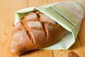 Close up of fresh whole wheat bread in green white napkin on wooden table