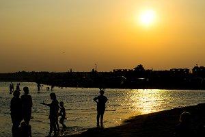 Silhouettes of tourists near sea
