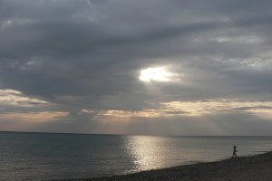 Sunset on sea with grey cloudy sky