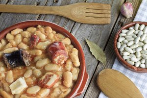 Spanish fabada in an earthenware dish and a wooden fork and knife