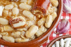 Spanish fabada in an earthenware dish with ingredients