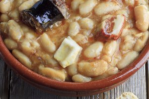 Spanish fabada in an earthenware dish with bread and garlick
