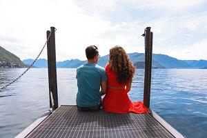 Couple sitting near lake Como, Italy