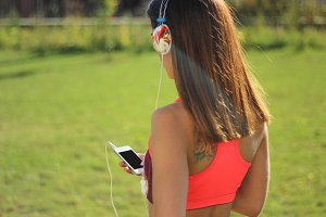 Young woman runner in headphones
