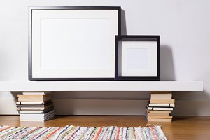 Black picture frames sitting on white shelf