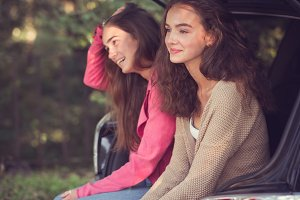Two girls sit in the trunk