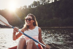 Smiling young woman kayaking