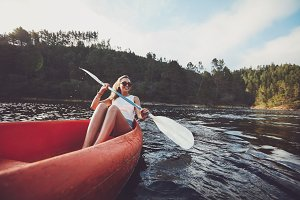 Happy young woman canoeing