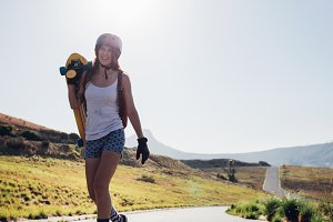 Woman walking with a longboard