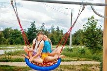 Best friends ride on a swing.