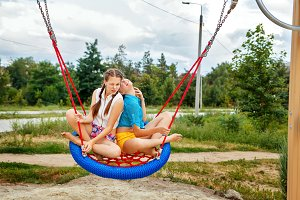 Best friends ride on a swing.