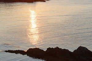 Sunset sea rocky coast view.