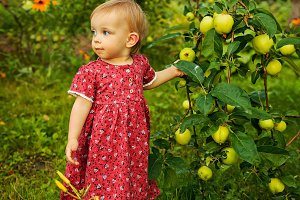 Little cute girl in garden. Summer