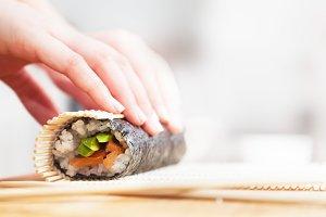 Preparing, rolling sushi.