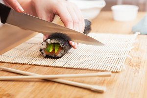 Preparing sushi, cutting.