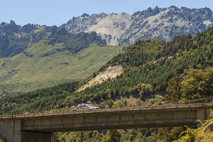truck on bridge by mountains